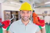 stock photo of hammer drill  - Happy repairman holding hammer and drill machine against workshop - JPG