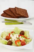 stock photo of fresh slice bread  - Fresh green salad in a plate and slices of brown bread placed on white tabletop - JPG