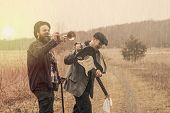 stock photo of gypsy  - Stylish gypsies play trumpet and electric guitar on a wilderness path - JPG