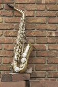 foto of lonely  - Lone old saxophone leans against brick wall outside abandoned jazz club - JPG