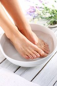 stock photo of foot  - A woman washes the feet in a bowl of water and salt to the foot - JPG