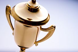picture of trophy  - Close up high angle view of a shiny gold trophy award to be awarded to the winner or champion in a competition with copyspace to the right - JPG