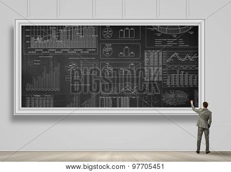 Rear view of businessman drawing business plan on banner