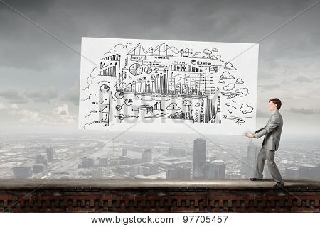 Young businessman carrying his great business plan in hands