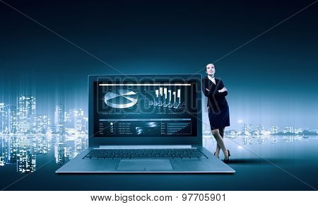 Young pretty businesswoman leaning on huge laptop