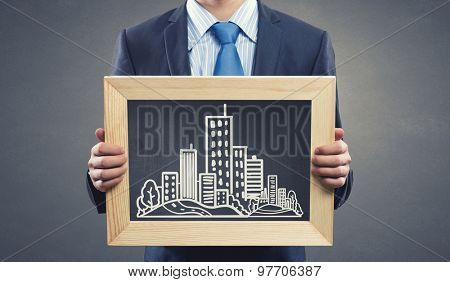 Close up of businessman presenting building model
