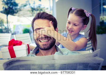 Daughter offering her present to her dad in the cafe
