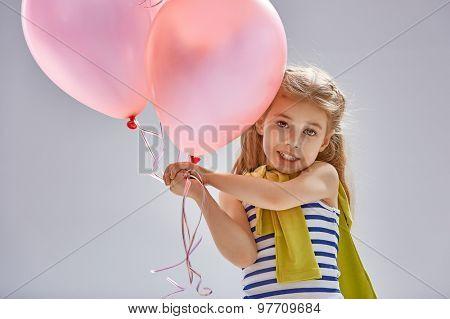 little girl holding pink balloons