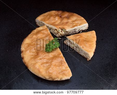 Chicken And Potato Pie With A Segment Cut Out Against Black Marble Background