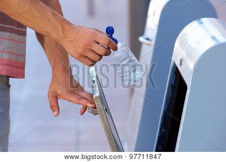 Male Hand Putting Plastic Bottle In Recycling Bin