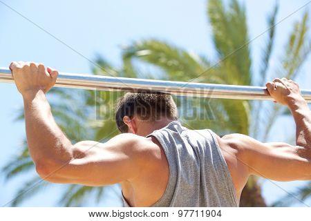 Man Exercising On Pull Up Bar Outside