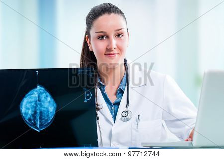 Young Female Doctor With X Ray And Laptop At Desk.