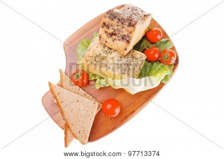 two smoked cheeses on wood with vegetables