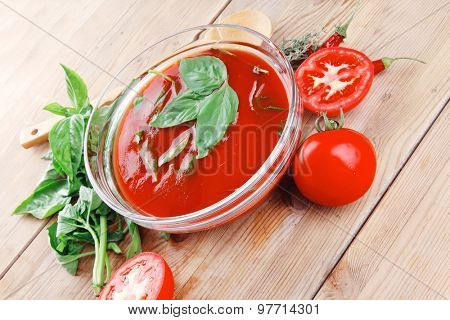 diet food : hot tomato soup with basil thyme and raw tomatoes in transparent bowl over red mat on wood table ready to eat