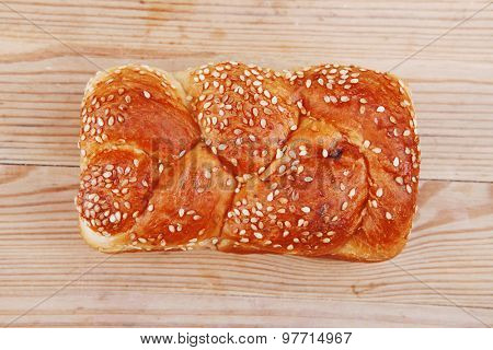 hot bun of light wheat bread topped by sesame seeds on wood