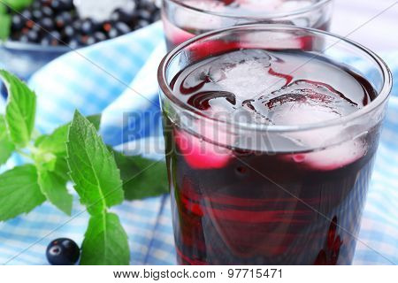 Glasses of fresh blackcurrant juice with ice cubes on checkered napkin, closeup