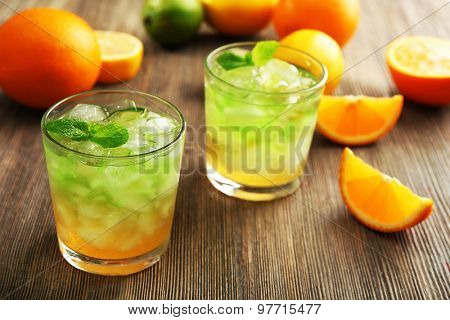 Glasses of lime juice with orange on wooden table, closeup