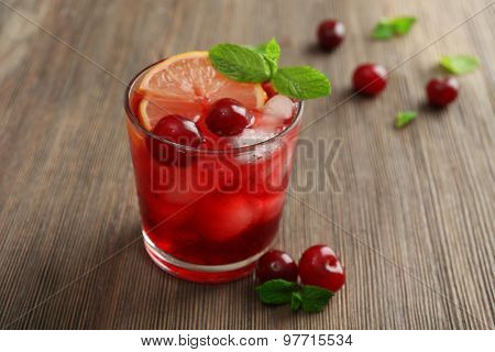Glass of cherry juice on wooden table, closeup
