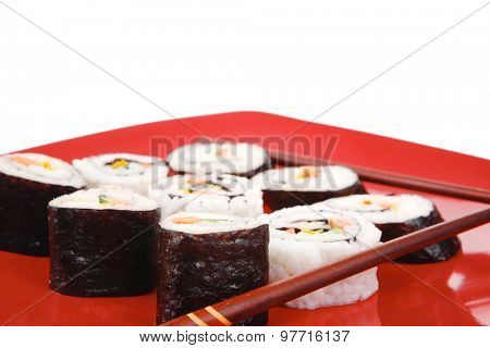 Japanese traditional Cuisine - Rolls with Cucumber , Cream Cheese with raw Tuna and Salmon inside. on red dish with sticks isolated over white background