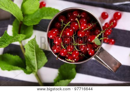 Ripe red currants in metal mug on table, closeup