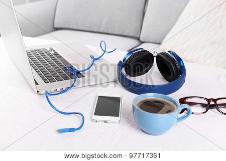 Headphones and other devices on wooden desktop at home