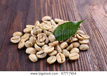 Green coffee beans with leaf on wooden background