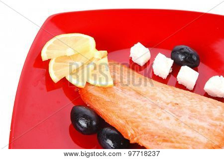 roast salmon fish meat fillet with lemon black greek olives white goat cheese on red plate isolated over white background