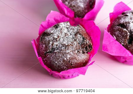 Chocolate cupcakes in pink paper on wooden table, closeup
