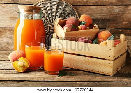 Ripe peaches and juice on wooden background