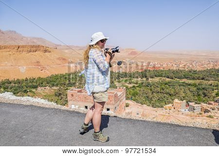 Female tourist taking pictures of Tinerhir - town near Todgha Gorge, Morocco