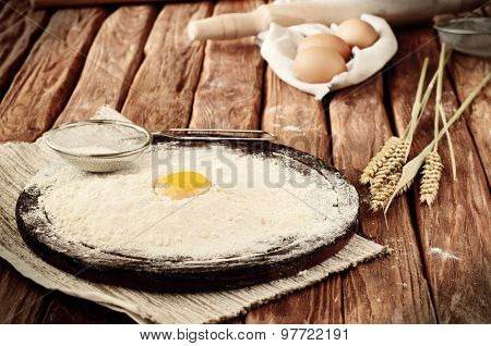 Egg yolk in flour close up on a wooden table