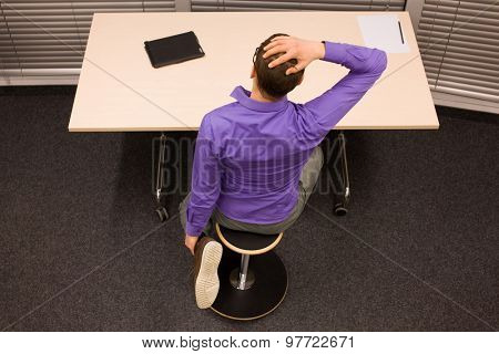 man exercising during short break in work at his desk in office - back view