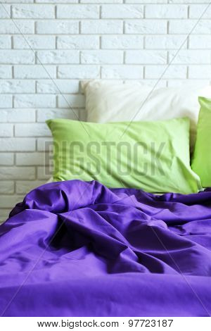 Comfortable bed with pillows and blanket in bedroom