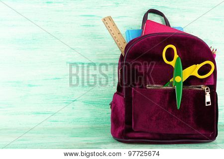 Backpack with school supplies on wooden background