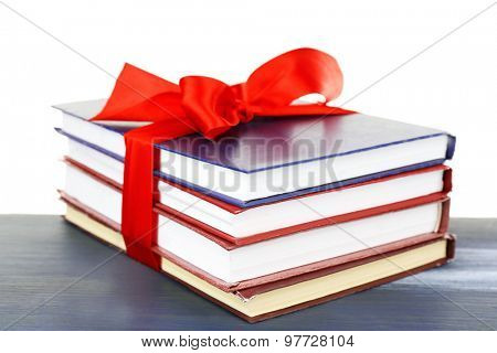 Stack of books with ribbon on light background