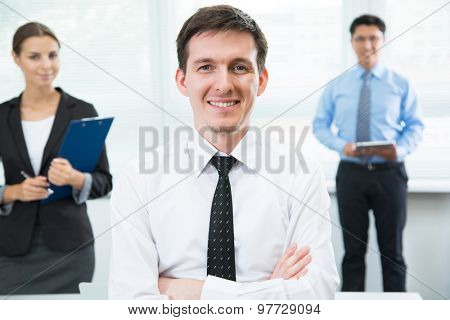 Happy businessman with team on the background