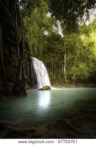 Vertical nature background of tropical waterfall in jungle forest with warm sunlight shines through trees and leaves
