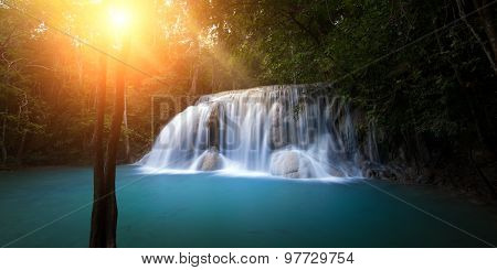 Sunlight in forest with waterfall