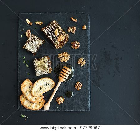 Honeycomb, walnuts, bread slices and honey dipper on black slate tray over grunge dark backdrop, top