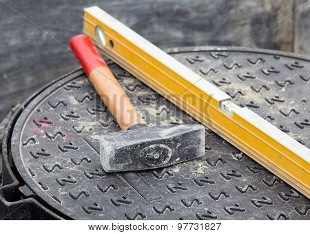 Hammer And Level On Manhole Cover