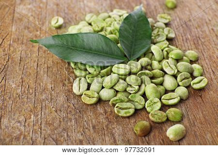 Heap of green coffee beans with leaves on table close up
