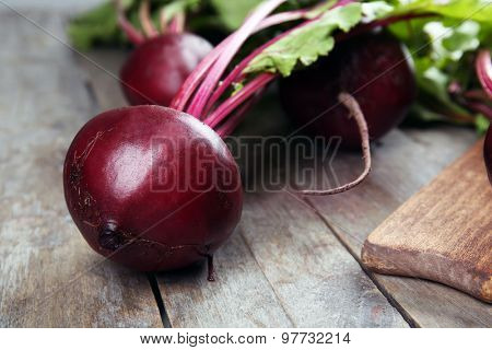 Young beets with leaves on wooden table close up