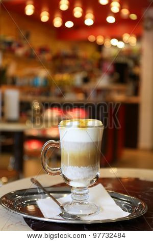 Glass of latte coffee on metal tray in cafe