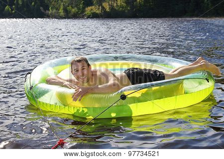 Man On Lake With Swim Ring