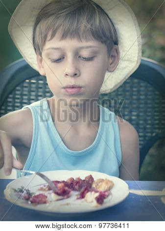 young boy with old hat eating