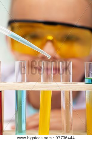 Young student in chemistry class - closeup on test tubes with colorful chemical solutions