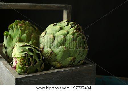 Artichokes in wooden basket on dark  background