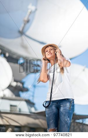 Happy Young Woman In Hat Listening To The Music In Vintage Music Headphones And Dancing Against Back