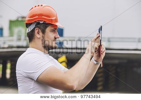 Builder Man Working With A Tablet In A Protective Helmet