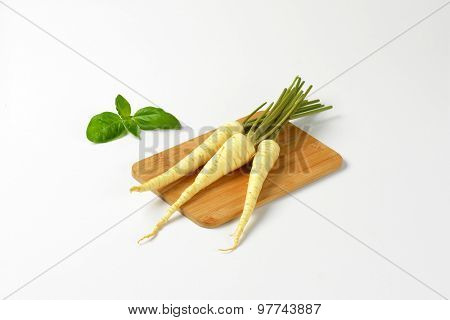 white parsley roots on wooden cutting board